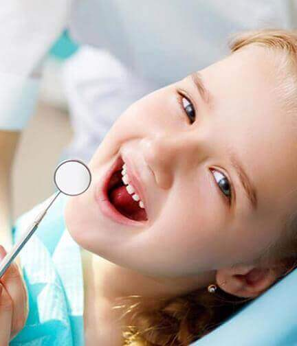 Young girl smiling at camera with mouth open for dental cleaning