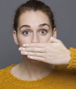 Woman looking nervous, covering mouth because of bad breath